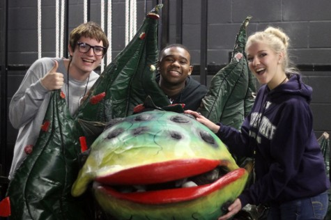 Senior Philip Robinson, junior Jenna Boyd and freshman Nate Courtney pose around Audrey II, the plant from Little Shop of Horrors.