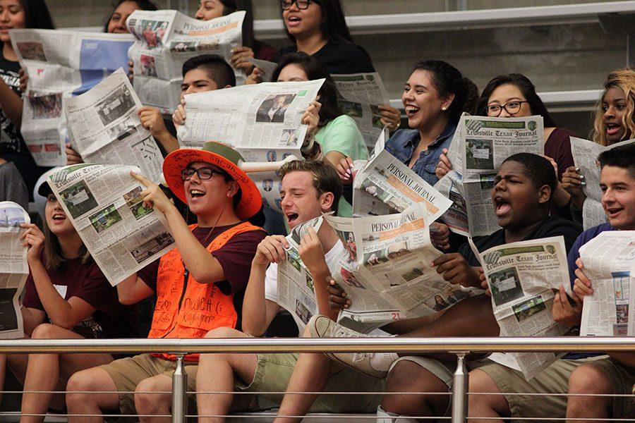 The Rowdy Crowd holds newspapers while the other teams names are being called.