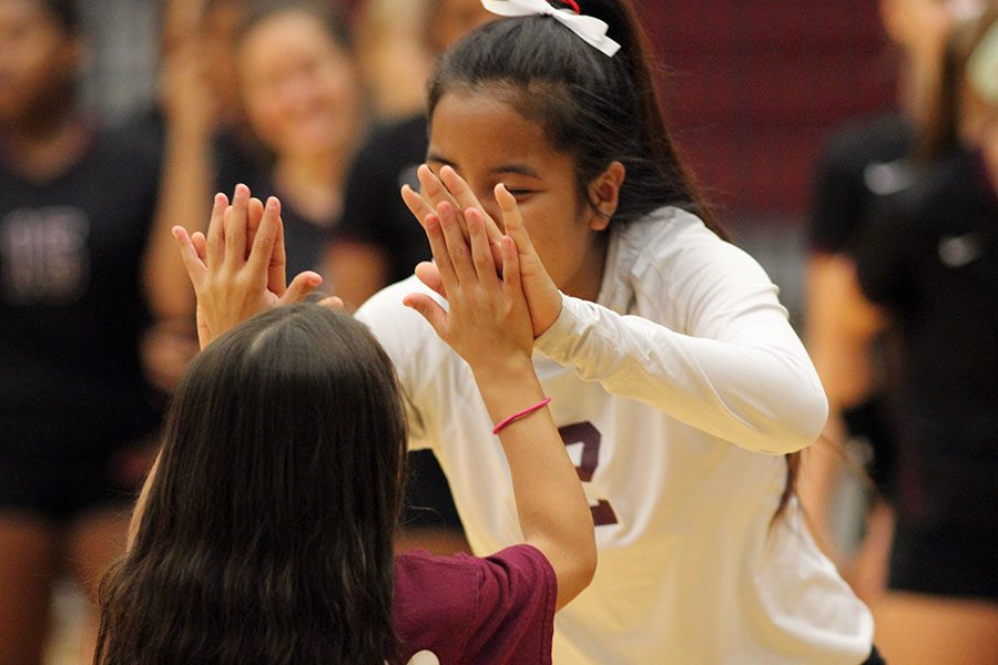 Senior Sui Caan (2) high fives the coachs daughter, Gabby Rodriguez, as the game begins.