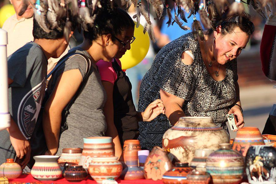 Attendees look at traditional crafts made by vendors.