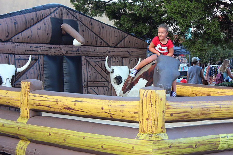 Children participate in different activities throughout the festival, including riding the mechanical bull.