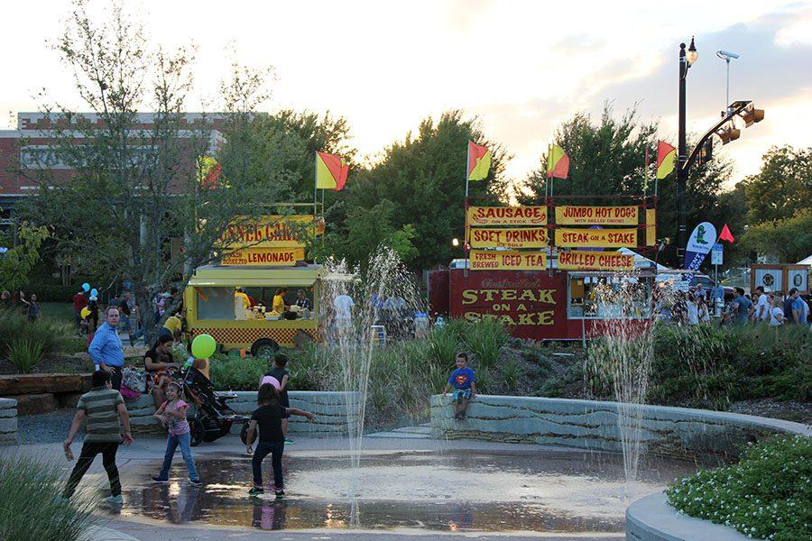 Children play along the water fountain as people enjoy the food trucks.