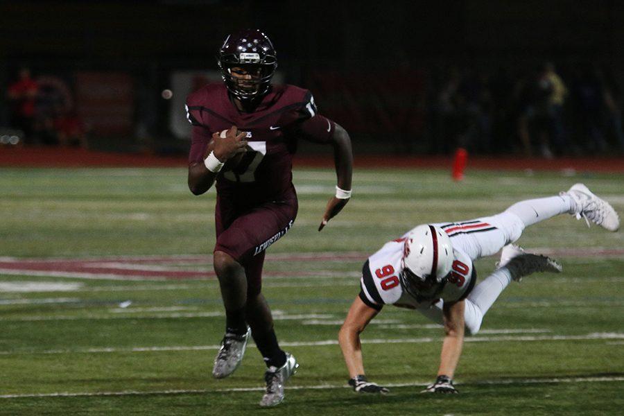 Senior quarterback Jarvis Brooks (17) runs the ball while Marcus High Schools senior defensive end Brett Brown (90) misses the tackle.