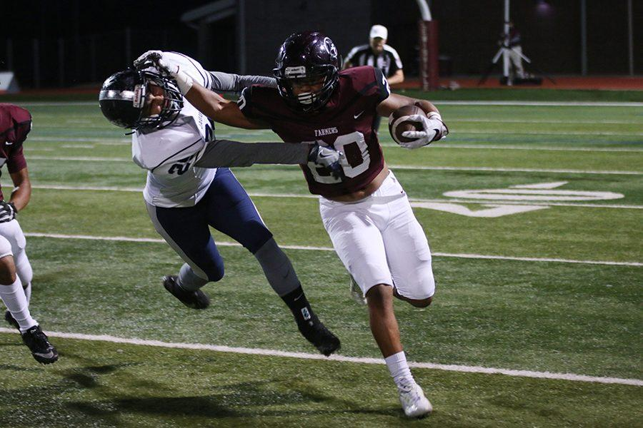 Junior running back DeMondrick Hunter (20) blocks Flower Mounds defensive player while running the ball.