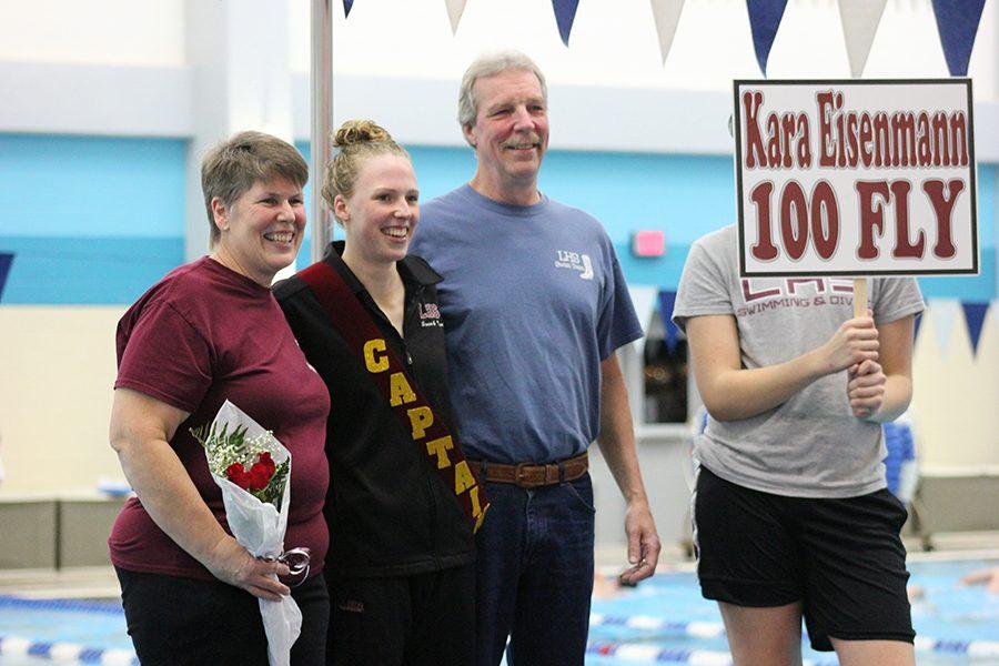 Swim captain senior Kara Eisenmann poses with her parents for senior night photo op.