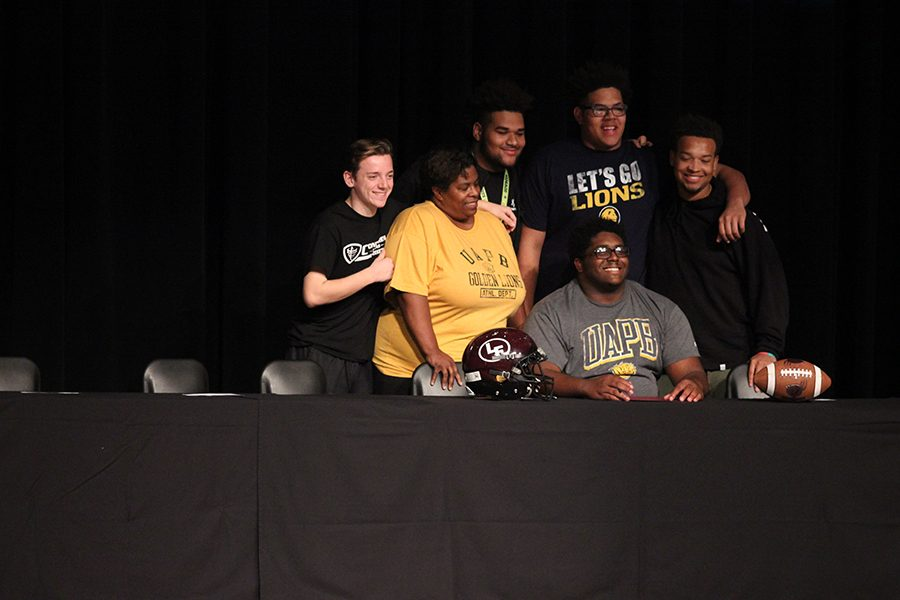 Senior Eric Jones signs to play football at the University of Arkansas at Pine-Bluff with his friends and mother by his side.