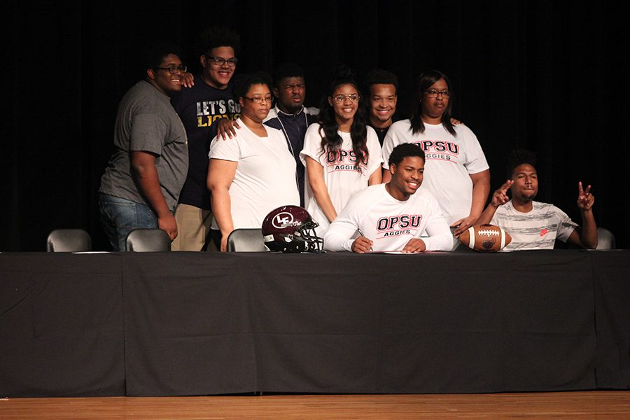 Dekevion Brown poses with family and fellow football players as he signs to play football at Oklahoma Panhandle State University.