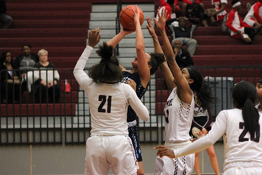 Junior Kennadi Lankford (21) and senior Amani Alston (40) attempt to block the opponent's shot.