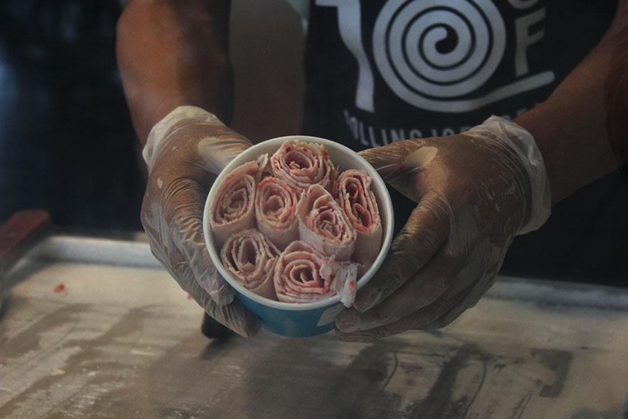 Employee LiuBao Chang shows the rolls of vanilla strawberry ice cream.