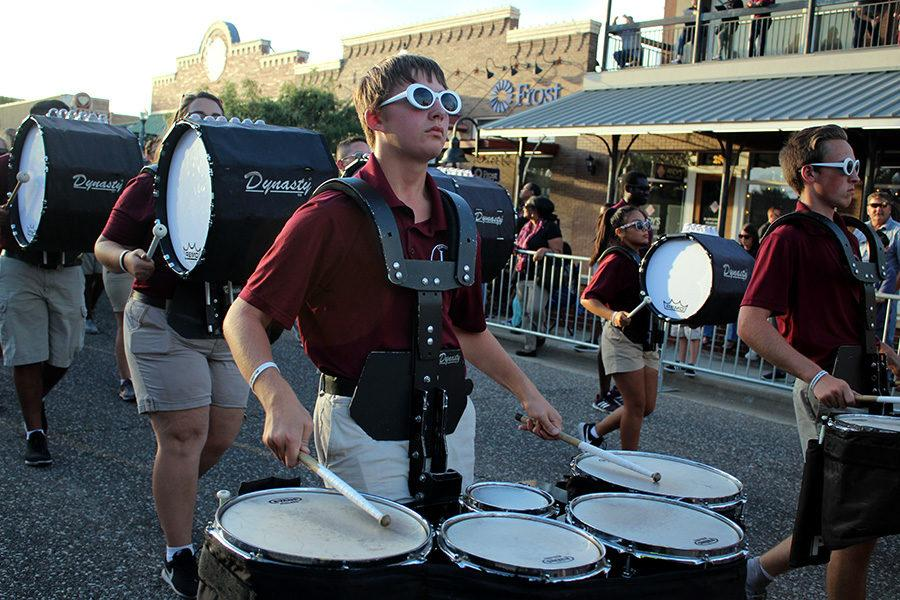 Senior Josh Hatter and the drumline play while marching during the parade.
