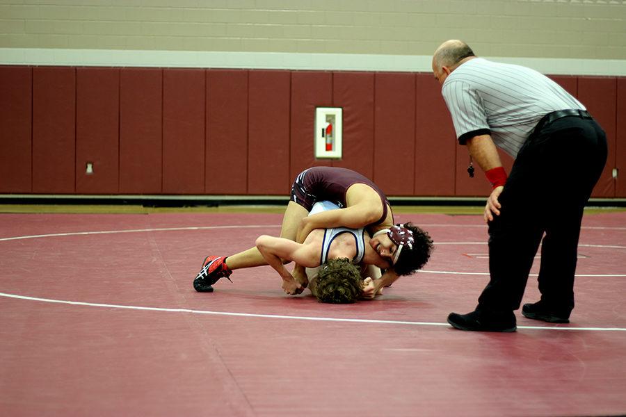 Sophomore Vinny Hill pins down a Flower Mound wrestler.
