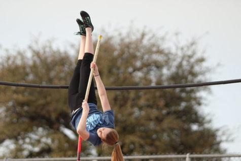 Senior Kaylee Packer prepares to twist her body to cross the bar.
