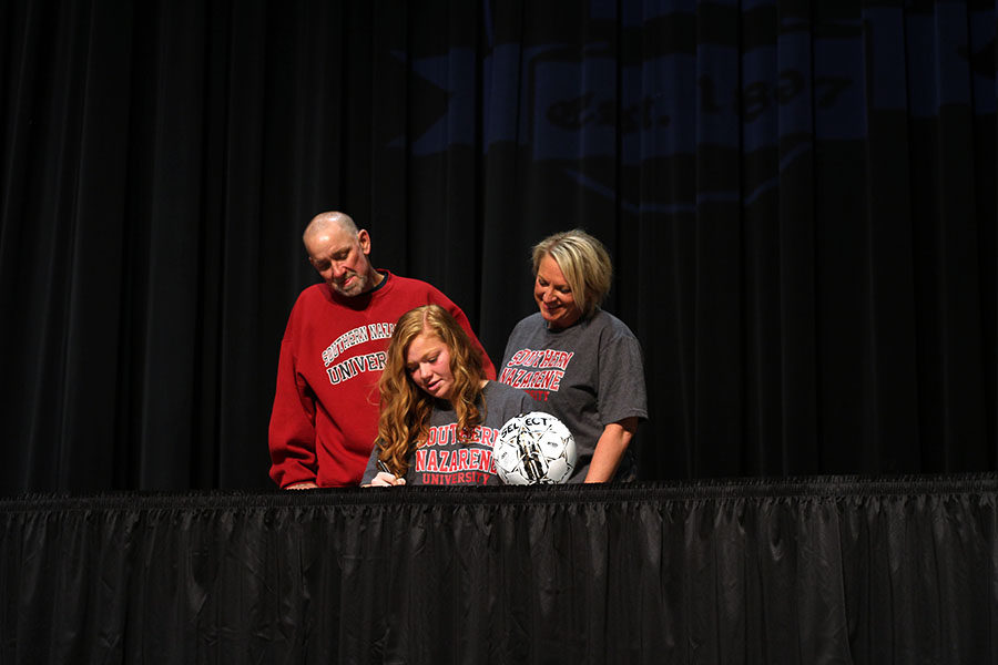 Senior Micaela Owen signs with Southern Nazarene University with her parents beside her.