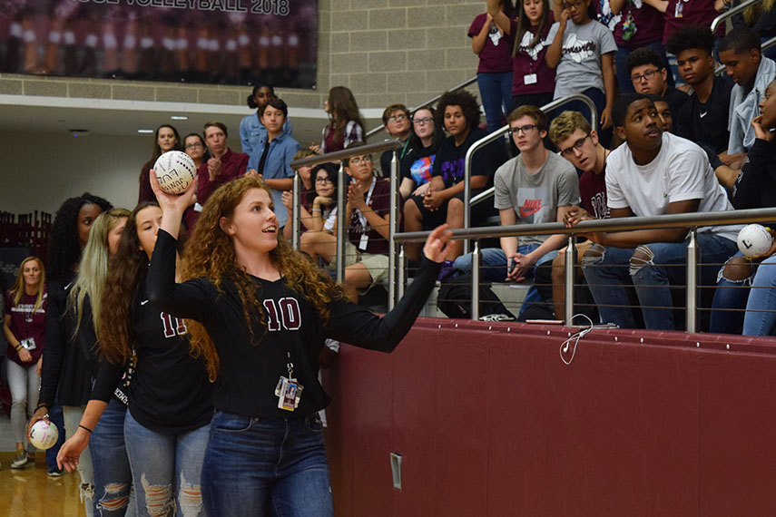 Junior Emerson Coburn (10) throws a volleyball toward the crowd.