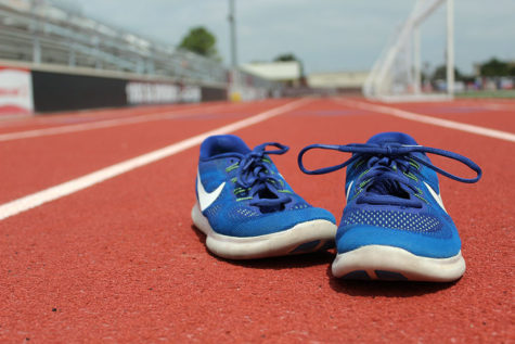 A pair of running shoes sits on the track.