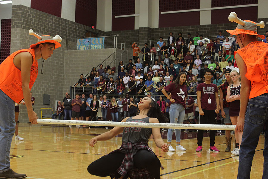 Sophomore Trinity Darby crouches for the limbo contest.