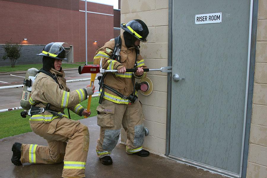 Marcus High School juniors Spencer Baltmanis and Ryan Moore attempt to jam open a door during practice.