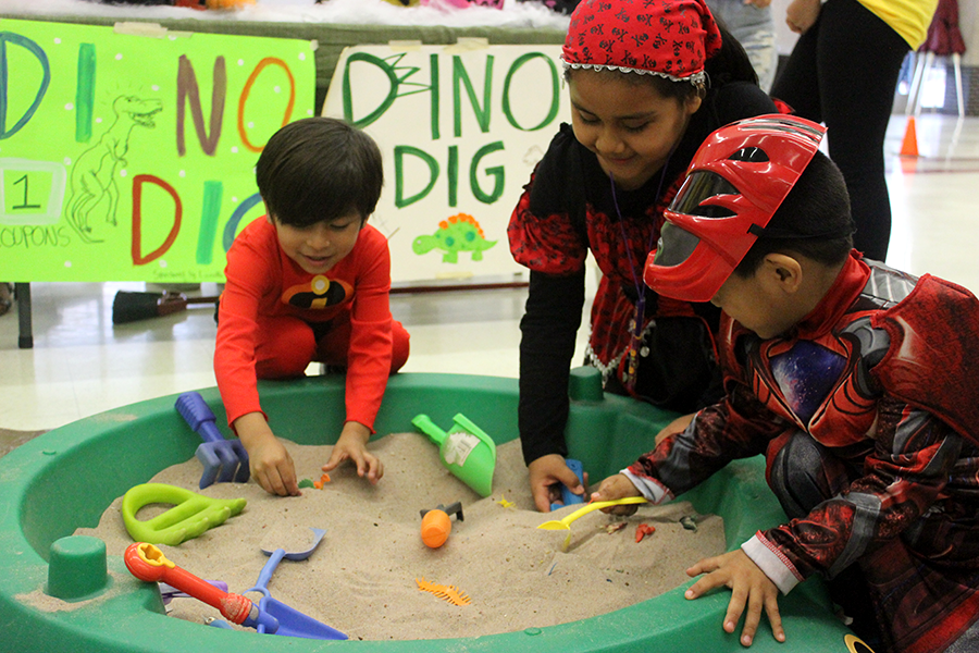 Children dig in a sand pit for little plastic dinosaurs.