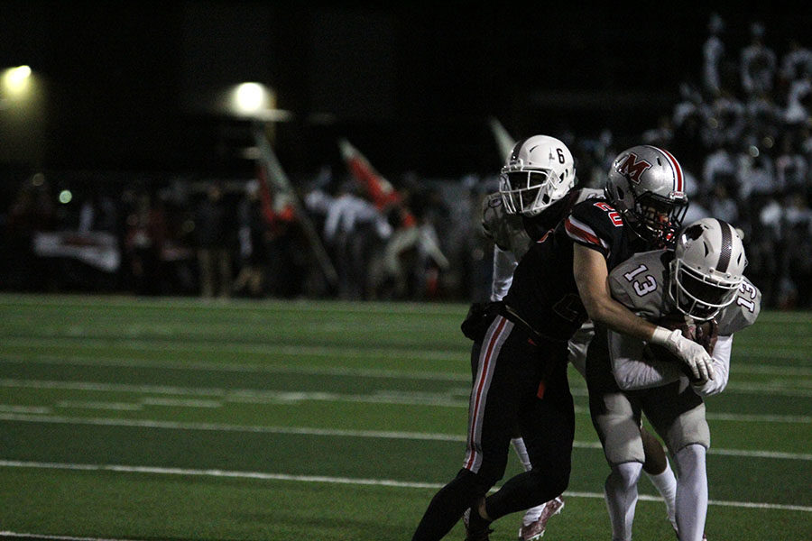 Senior Deshaun Kincaid (13) tries to push through a Marcus players hold while gripping the ball tightly.