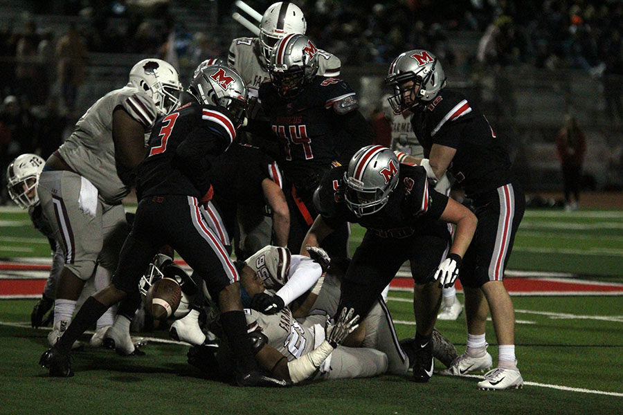 Senior Josh Lockhart (20) gets tackled by Marcus players and loses grip of the ball.