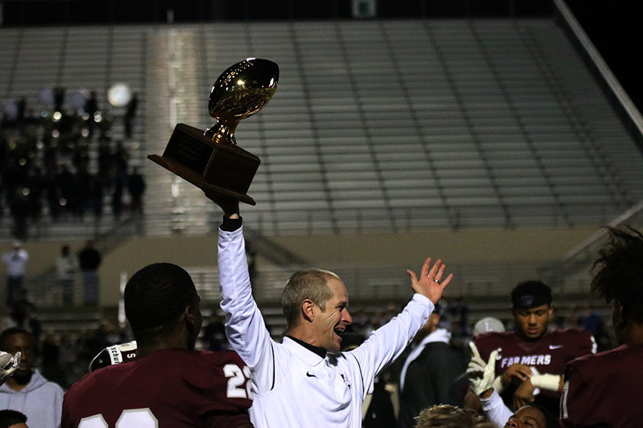 Head coach Michael Odle holds the bi-district trophy.