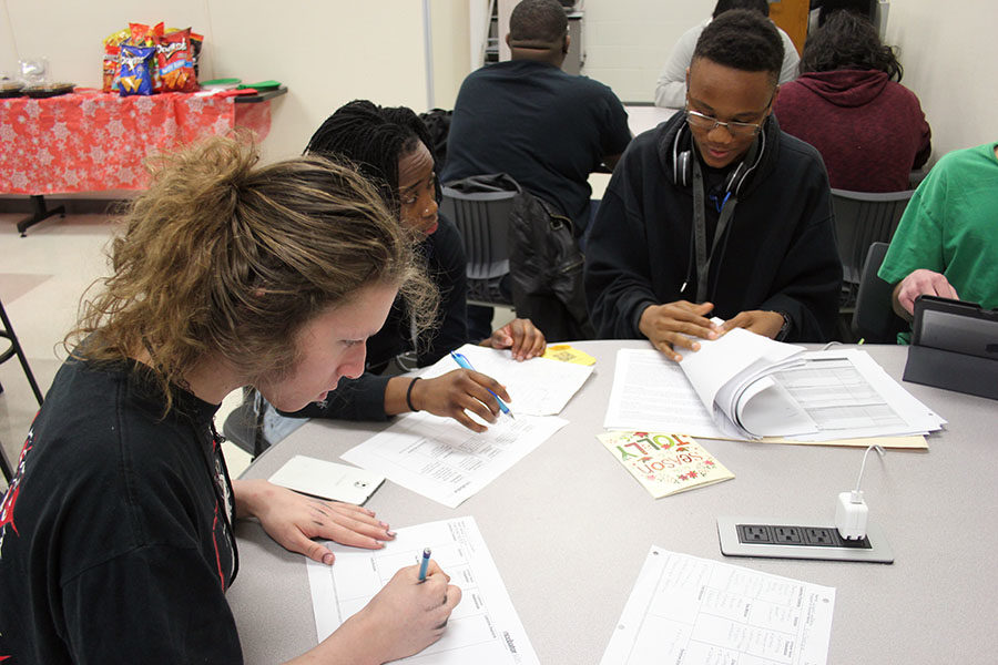 Senior Nala Hemingway and juniors Isaiah Williams and Mica Adams evaluate the research theyve done for their project during class on Wednesday, Dec. 19.