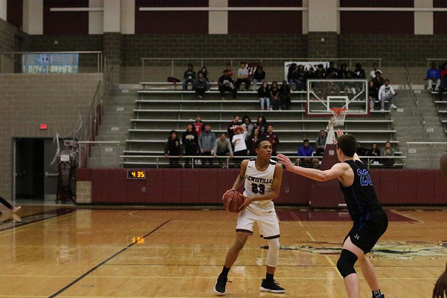 Sophomore guard Kylin Green (23) looks for an opening while trying to get through the Bryon Nelson defense.