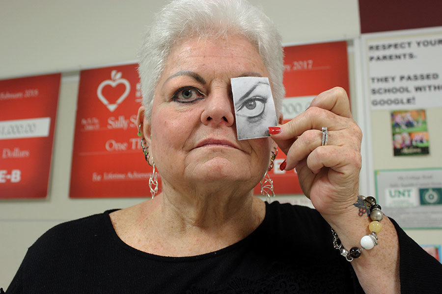 Debate teacher Sally Squibb holds a picture of her eye she had surgery on.