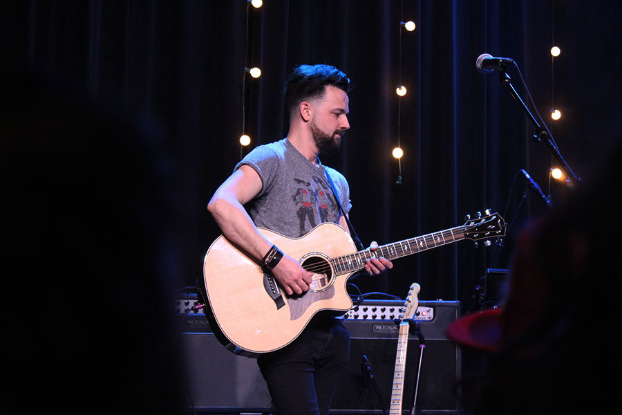 Billy Moran plays an acoustic guitar during