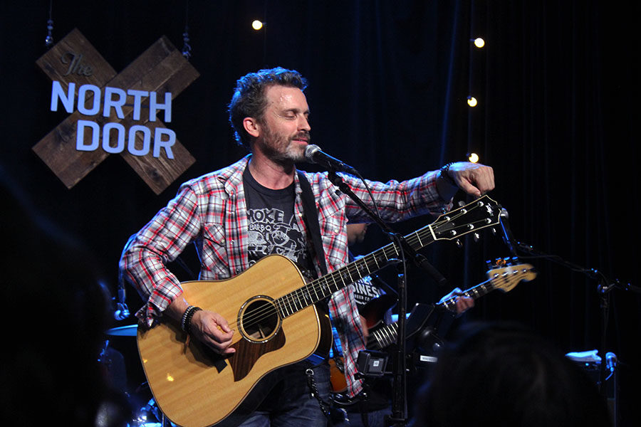 Rob Benedict talks to fans while tuning his acoustic guitar before singing