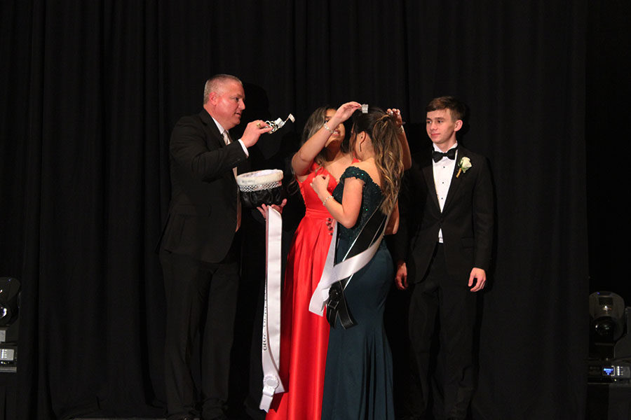 Principal Jeffery Kajs hands a crown for Prom Queen Jackie Hernandez to be crowned.