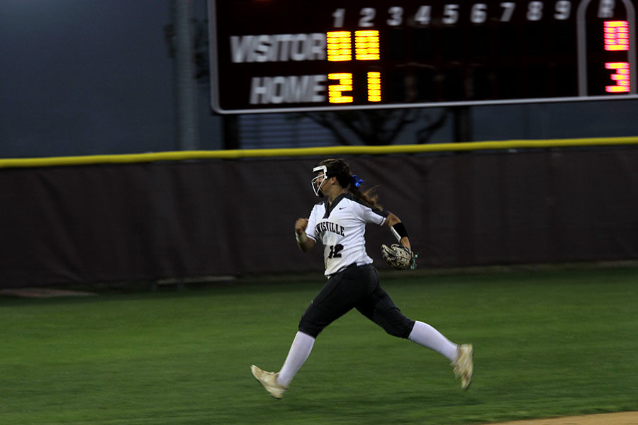 Sophomore Emilee Till sprints to  catch the fly ball before the other teams member passes the bases.