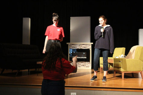 Senior Avery Brooks helps junior Sophia Cauduro and sophomore Madelyn Bloom on their singing during What is this feeling? for Wicked.