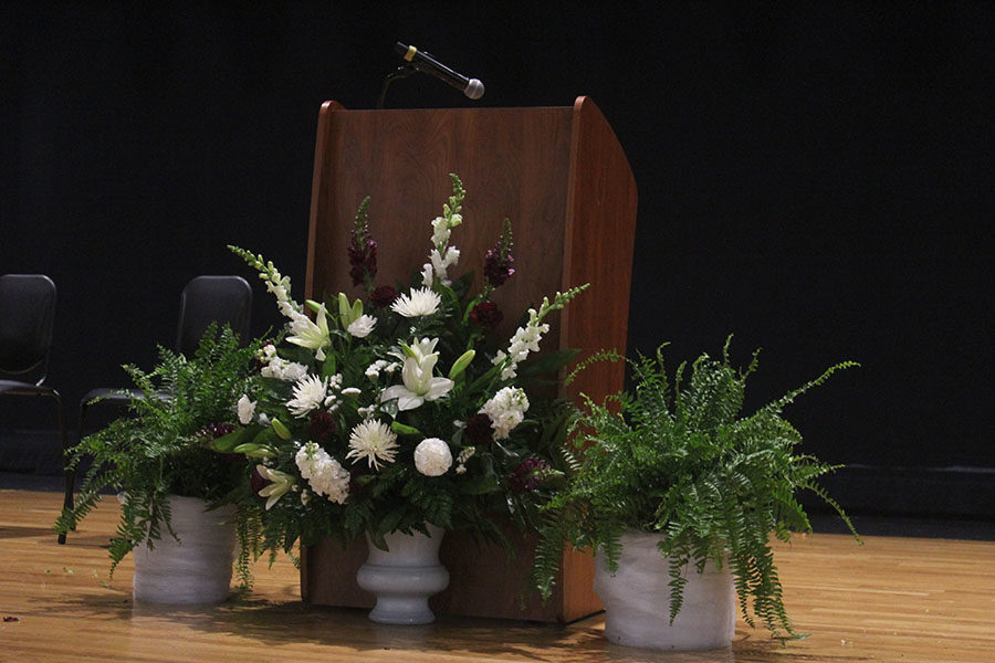 Decorated plants rest by the stand and are center pieces on the stage.