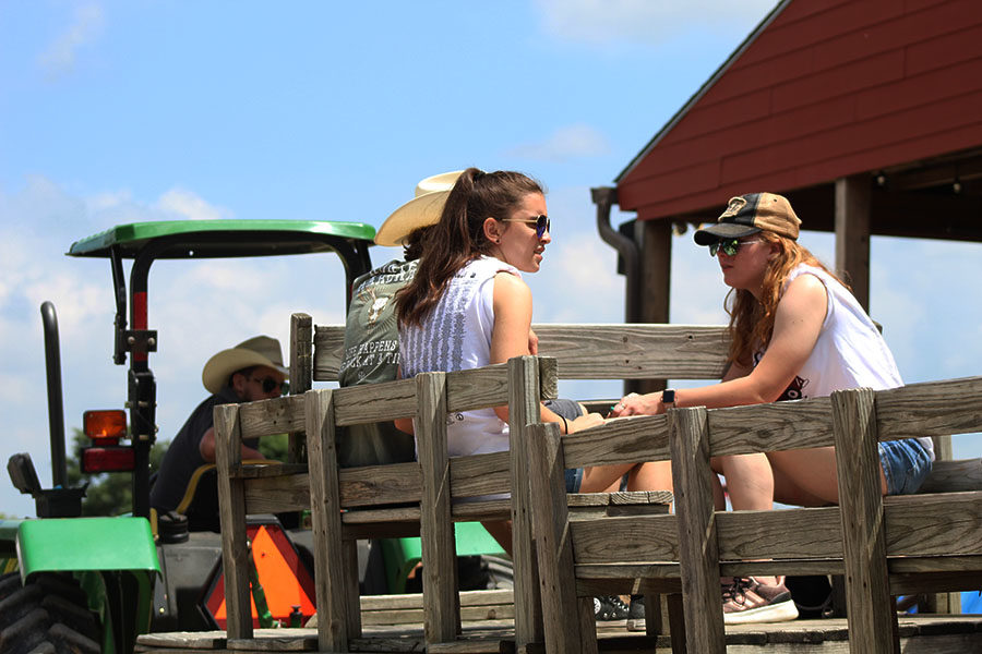 Seniors Kaylee Mitchell and Cassie Mosley ride on the wagon provided by Circle R Ranch.