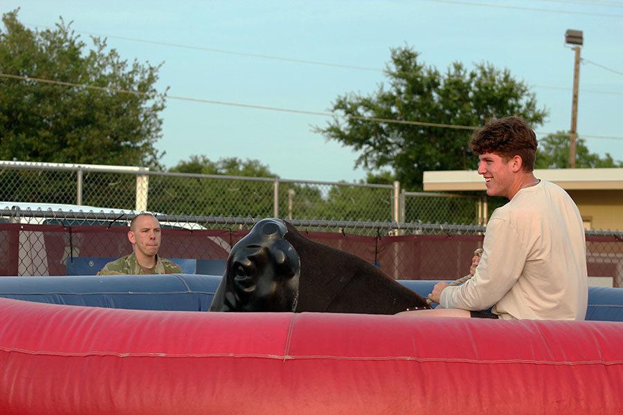 Senior Joey Rochette laughs as he rides the mechanical bull.