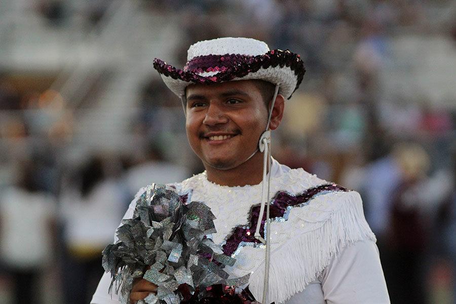 Senior Farmerette lieutenant Erick Sanchez smiles as he shakes his poms before the football game at Flower Mound on Friday, Sept. 27.