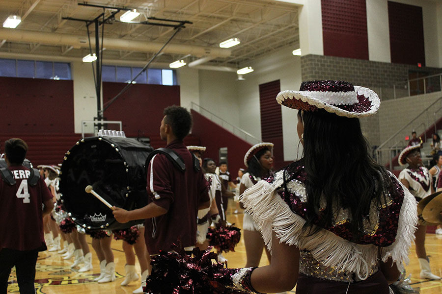 The Farmerettes perform their routine as the marching band marches along the way.