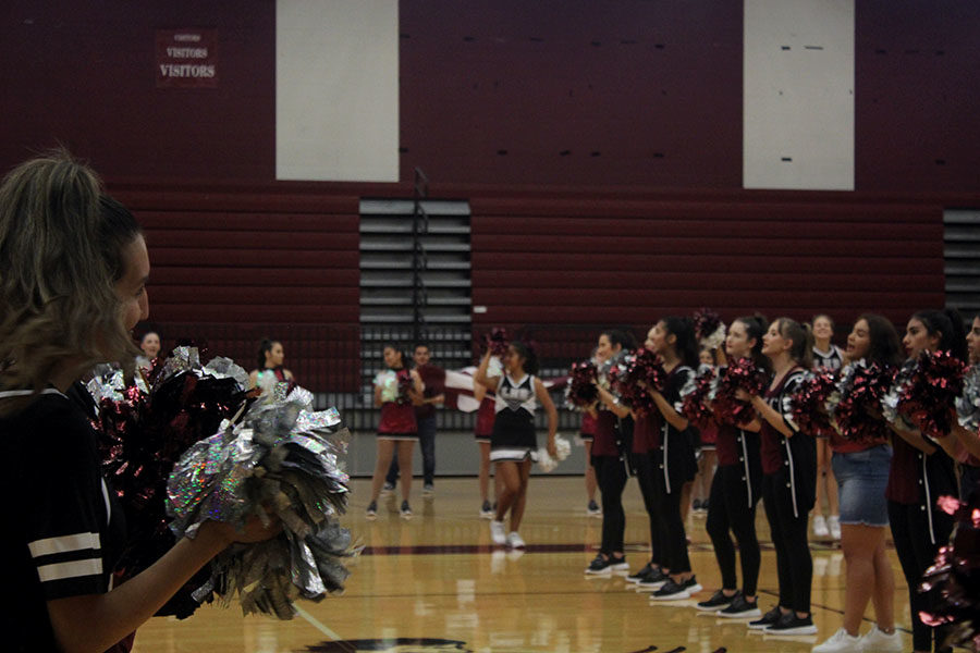 The Farmerettes making a pathway for the band and football players