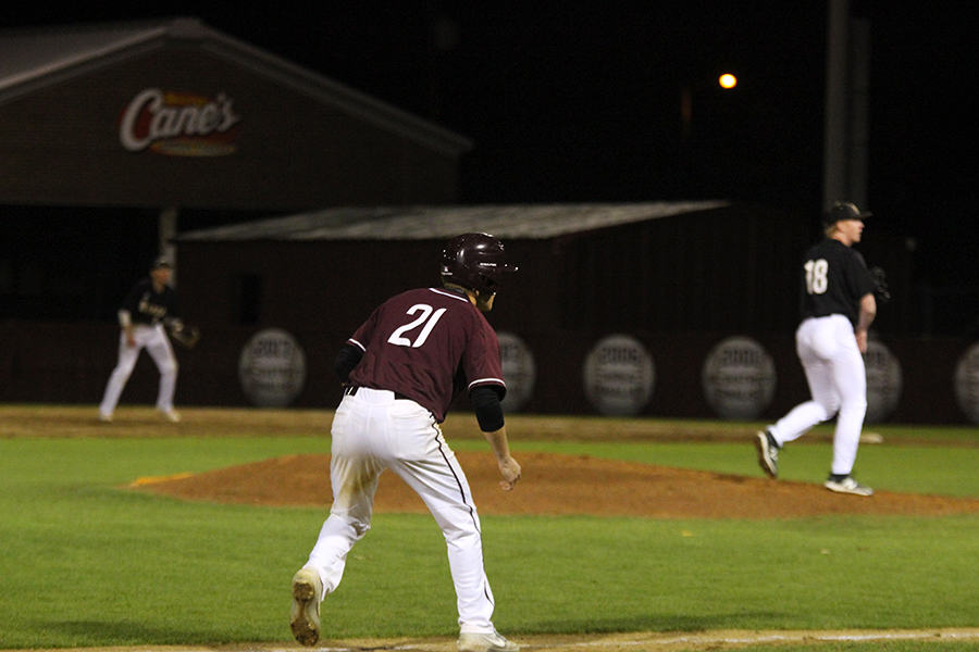 Senior Trey West (21) eyes a pitch in anticipation to make a dash toward home from third.
