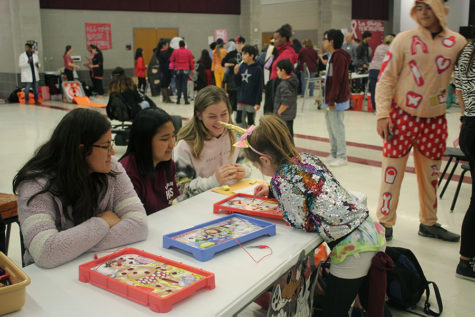 Student volunteers senior Monica Acosta, junior V Tra and senior Claire Fowler help procter the Operation game booth.