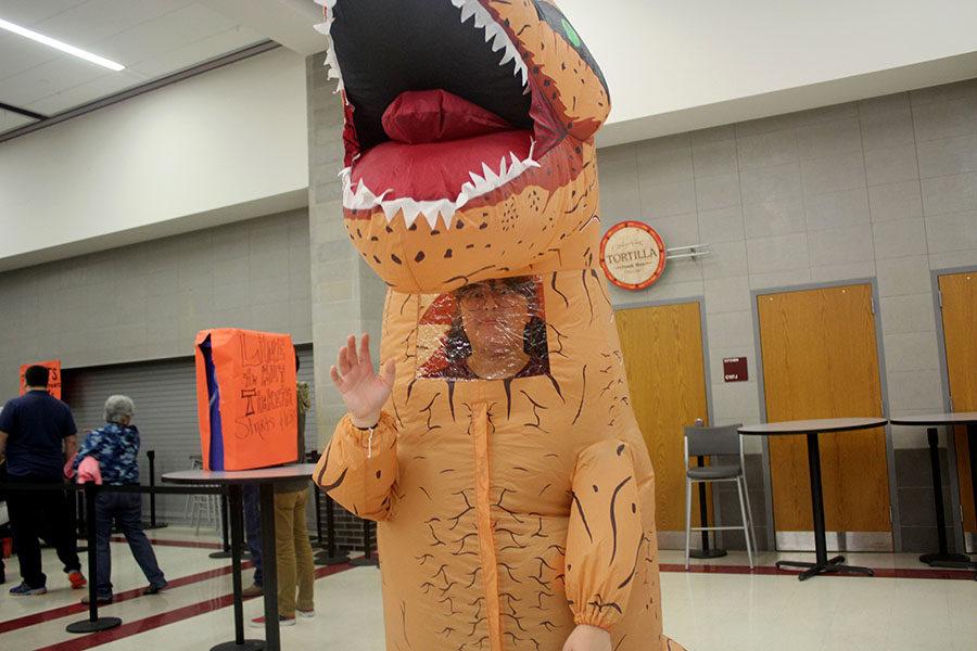 Senior Kaylie Davis waves from her dinosaur costume.