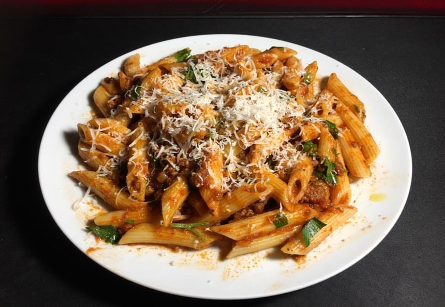 A creamy bolognese pasta with a shredded cheese topping sits on a plate after being made by Senior Erick Nguyen.