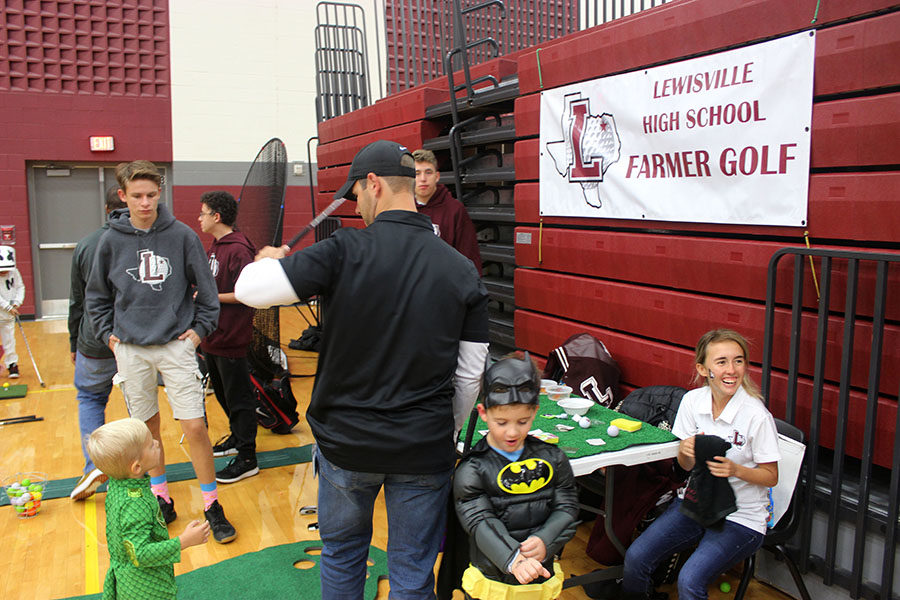 Kids enjoy the mini-golf booth at the Halloween carnival.