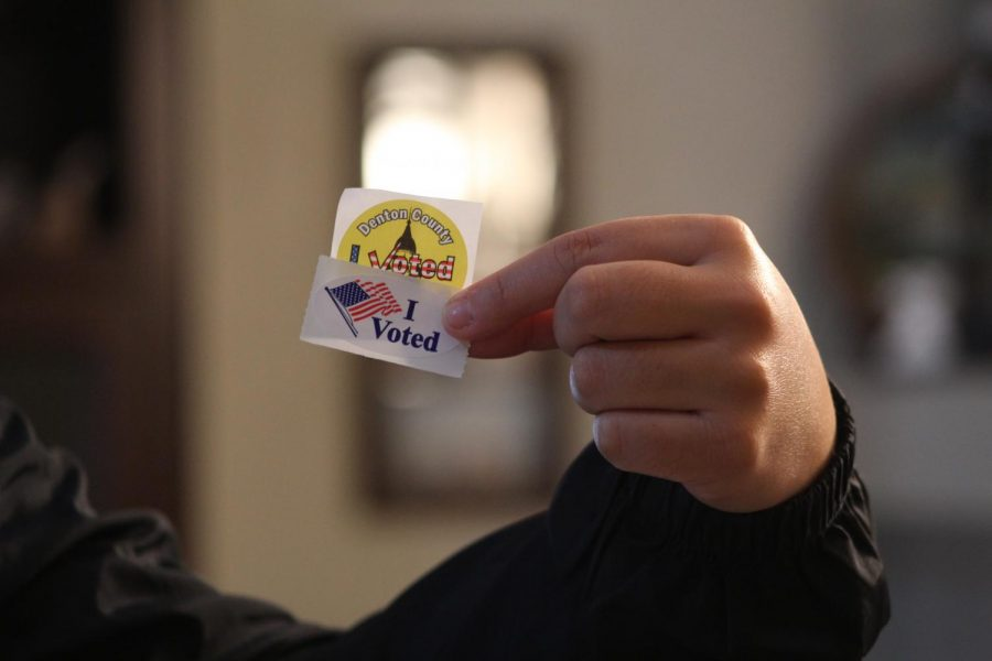 An early voter poses with voting stickers from Denton County.