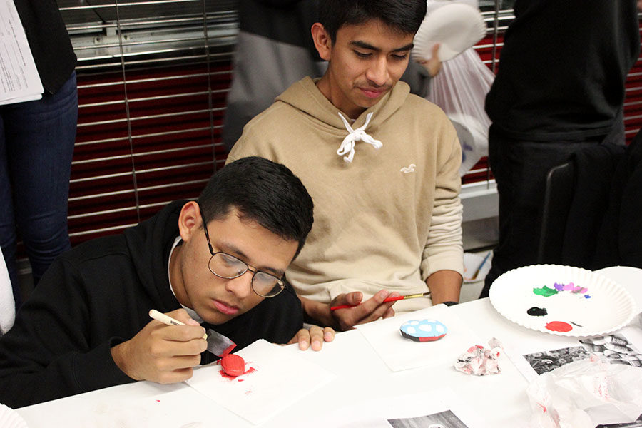 Students paint rocks at the Halloween carnival.