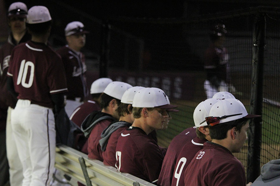 The team sits and observes the game from the dugout.
