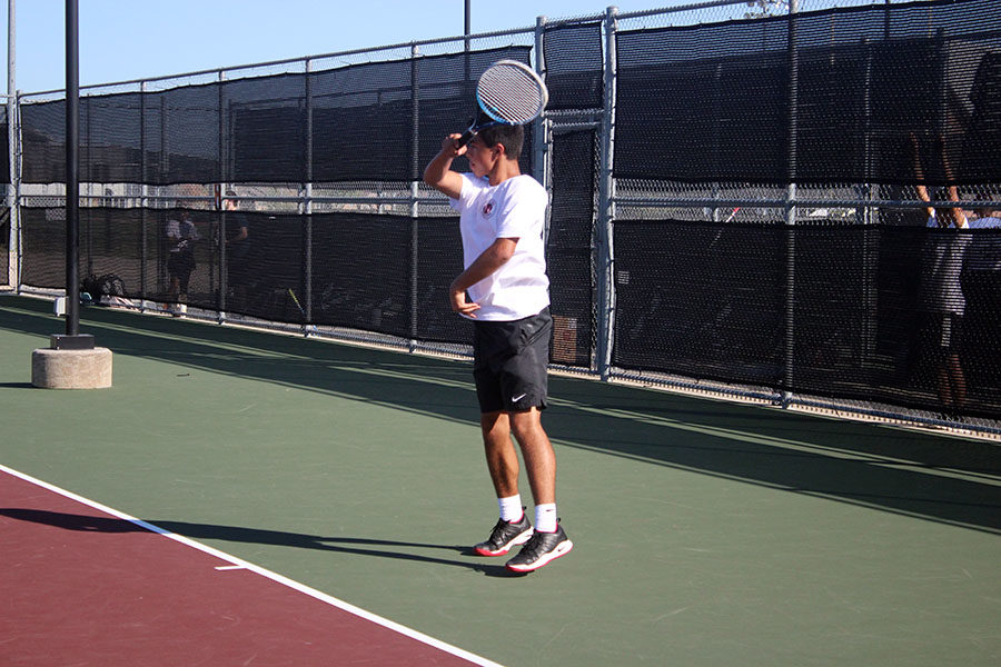 Senior Andre Cardenas finishes a forehand behind the baseline.
