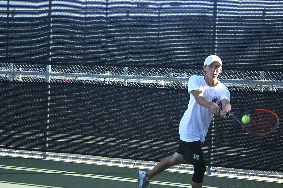 Senior Collin Erickson returns ball with a backhand.