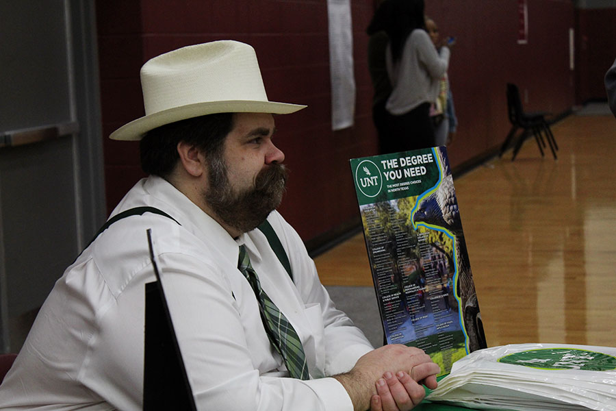 The UNT representative dons a cowboy hat as a crowd of students gathers around his booth.